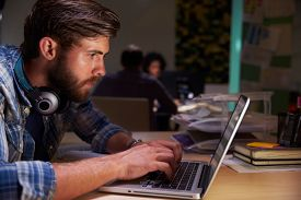 stock photo of late 20s  - Office Workers At Desks Working Late On Laptops - JPG