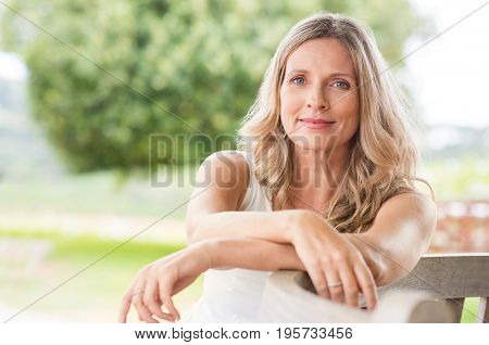 poster of Happy senior woman relaxing on bench in the lawn. Close up face of a mature blonde woman smiling and