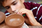 stock photo of molding clay  - boy teen potter clay bowl working in pottery workshop traditional arts - JPG