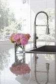 vase of pink peonies and chartreuse chrysanthemums on sink of modern kitchen - reflection in granite