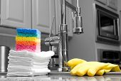 colorful sponges, cloths, and yellow gloves in modern kitchen - housework - partially toned image