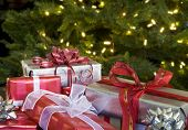 stock photo of christmas-present  - red and white christmas presents with bows by tree - JPG