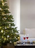 two red drinks by christmas tree with lights, bows in modern living room