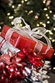 red christmas gift and ribbons by christmas tree lights