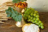Imagem de comunhão, mostrando um cálice de ouro com uvas e bolachas de pão