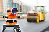 Construction surveyor equipment theodolite level tool during asphalt paving works with compactor rol