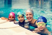 Group Swimming Lesson For Children On Indoor Swimming Pool, Toned Image poster