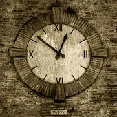 Old-fashioned clock on the side of an old brick wall, from a medieval village in europe with sepia t