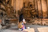 Tourist Girl Praying In Front Of  Buddha Statue poster