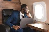 Attractive And Successful African American Businessman With Glasses Working On A Laptop While Sittin poster