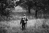 Single Re-enactor Dressed As German Wehrmacht Infantry Soldier In World War Ii Walking In Patrol Thr poster