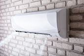 White Air Conditioner Blowing Cold Air On Brick Wall In Living Room poster