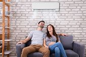 Happy Young Couple Sitting Under Air Conditioner On Couch At Home poster