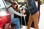 Smiling Young Husband Helping Her Disabled Wife With Crutches To Get Inside The Car poster
