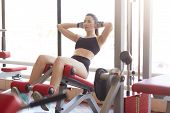 Image Of Attractive Athltic Woman Pumps Press On Simulator In Sports Gym, Tones Muscles, Liffting Up poster