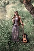 Beautiful Hippie Girl With Guitar Standing Near The Pond poster