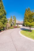 Beautiful exterior of newly built luxury home. Yard with green grass and walkway lead to front entra poster