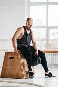 Perspiring Male Athlete Resting After Intense Cross Workout. Tired Sportsman Relaxing On Wooden Box  poster