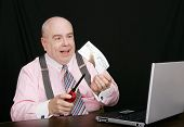 pic of paycheck  - business man in a pink shirt lighting his paycheck on fire - JPG