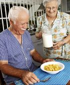Grandparents eating cereal corn flakes at kitchen.