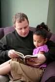 stock photo of father daughter  - Father reads a book to his young daughter - JPG