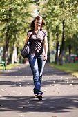 Full length, walking woman in blue jeans