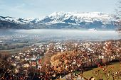 Town Of Vaduz The Capital Of Liechtenstein, Fog Above The River And Snow Mountains Of Switzerland Ov poster