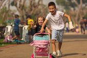 Boy And Girl Play A Game Of Children Playing In A Pram In A Park. Childrens Friendship. Children Wi poster