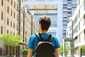 Rear View Of A Young Man With Backpack Just Arrived In A Big City And Looking To Modern Buildings Wi poster