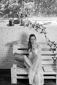 Pretty Girl In White Wedding Dress And Retro Hairstyle. Pretty Girl Read Book On Bench poster
