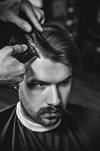 Young Handsome Barber Making Haircut For Attractive Bearded Man At Barbershop. Black And White Or Co poster