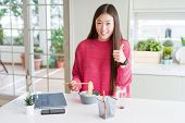 Beautiful Asian woman working using laptop and eating asian noodles happy with big smile doing ok si poster