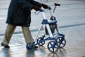 image of rollator  - An elderly woman walking on the street with her walking frame - JPG