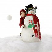 stock photo of snowball-fight  - An elementary girl tosses a snowball from behind a Christmas snowman - JPG