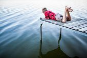 stock photo of dock a lake  - Boy laying on a dock by a lake - JPG