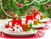 Photo of Christmas table decoration, festive dinnerware with candles and red cups for tea in decorat