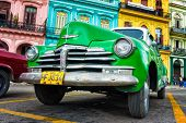 HAVANA-NOVEMBER 28:Old Chevrolet in front of colorful buildings November 28,2012 in Havana.Thousands