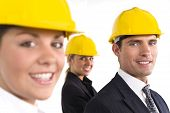stock photo of hard_hat  - A selective focus industrial concept shot showing 2 women and a man dressed in hard hats - JPG