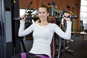 Happy young woman exercising on a shoulder press in fitness center