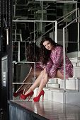 Beautiful woman in pink dress sitting on stairs