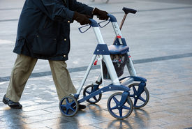 picture of rollator  - An elderly woman walking on the street with her walking frame - JPG
