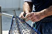 man knitting fishing net