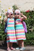 stock photo of identical twin girls  - Cute little twin girls dressed in identical dresses and headscarves and wearing sunglasses standing in the sunshine making V - JPG
