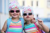 image of lollipop  - Two little identical twin girls with their blond hair tied up in bandannas and wearing sunglasses smiling happily at the camera - JPG