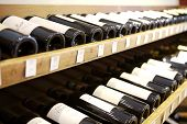 foto of wine bottle  - Wine bottles displayed on rack in wine shop - JPG