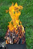 foto of brazier  - tongues of flame over burning wood in outdoor brazier - JPG