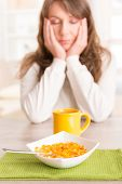 Sleepy young woman trying to eat cornflakes and drink morning coffee