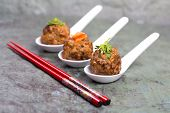 Asian meatballs, garnished with pea shoots in three ceramic spoons with chopsticks, against natural slate background.