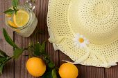 Fresh Squeezed Lemonade on a rustic wooden table with lemons and a yellow sun hat. Horizontal format