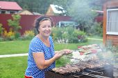 Mature woman Cooking On A Barbeque in the garden